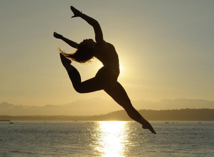 One-click: Gymnast catching the light over Puget Sound with the Olympic Mountains and golden water for a backdrop. Jerry and Lois Photography