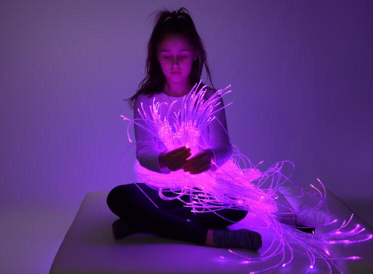 Playlearn product, young girl intrigued by glowing fiber optic product