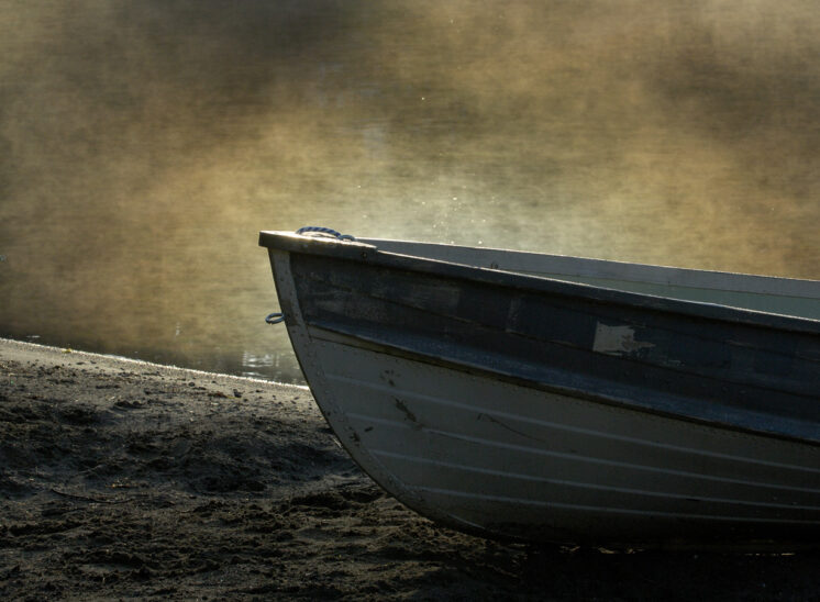 Break of dawn, sunlight creating magical sparkles and textures in the fog behind a simple rowboat. Jerry and Lois Photography