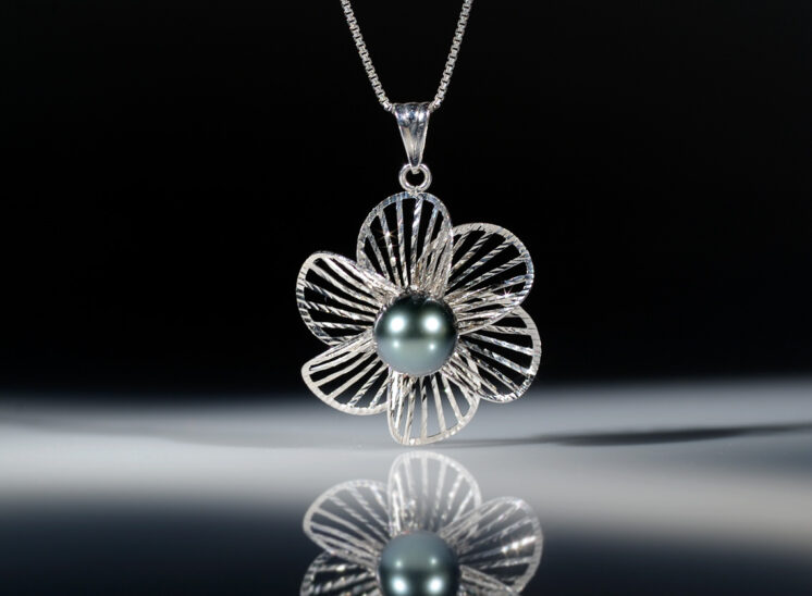 A single black pearl pendant with matching reflection. Jerry and Lois Photography