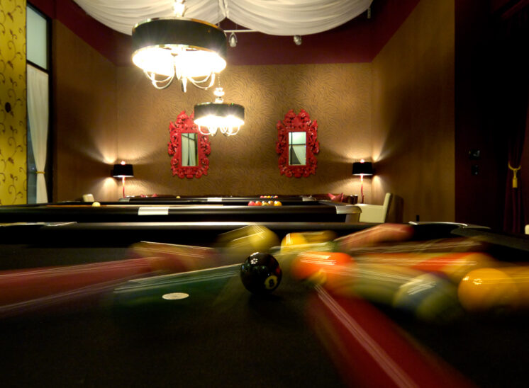 A perfectly moody setting for a motion-blurred break on a pool table, the 8 ball frozen in place. Camera-wise, literally a lucky break. © Jerry and Lois Photography