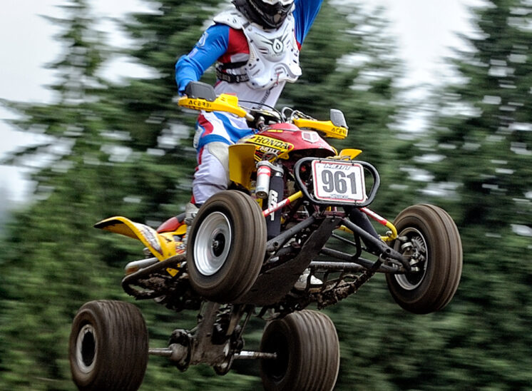 Part of a series for a Quad Motocross National Champion, demonstrating his amazing (and fearless) ability to catch air at 60+ mph. In sharp focus against a motion-blurred background. © Jerry and Lois Photography, all rights reserved