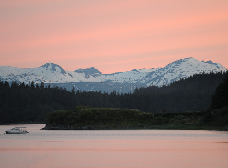 Near midnight in Juneau, in an everlasting sunset awash with pink. Mountains and a solitary boat framed by the glowing sky. Jerry and Lois Photography