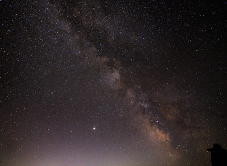The Milky Way, including the galactic core in the SE skies of central Washington with a close friend and observer silhouetted against the universe. Jerry and Lois Photography
