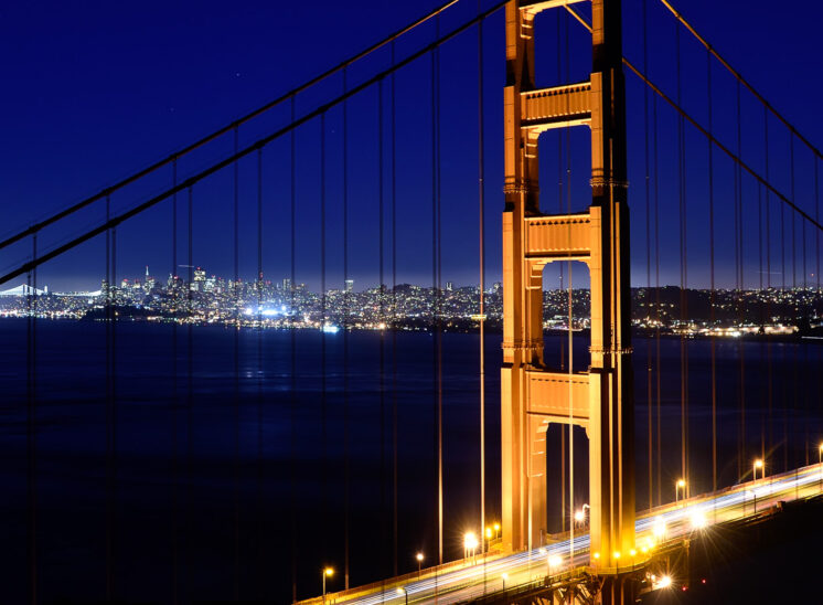 Golden Gate Bridge in golden glow and streaks of traffic, all framing the brilliance of nighttime San Francisco. Jerry and Lois Photography