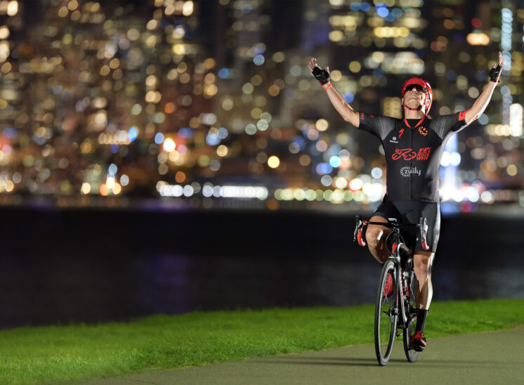 Cyclist claiming victory while fundraising in the fight against cancer, with the lights of Seattle glowing behind him. Jerry and Lois Photography