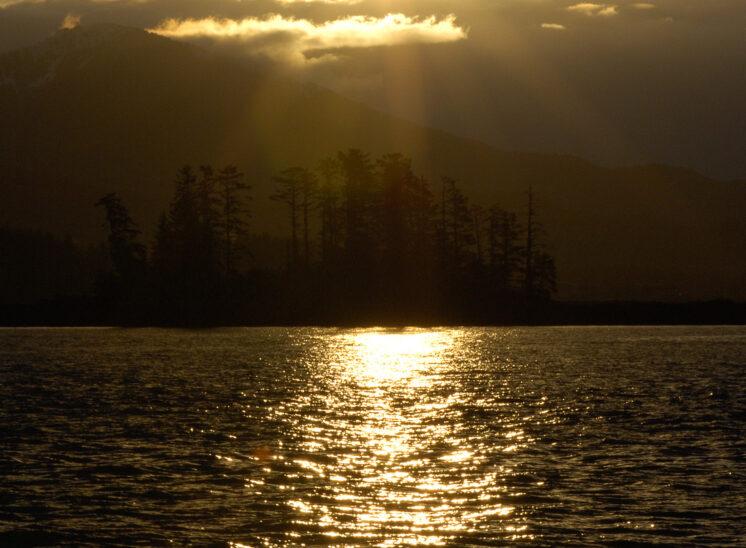The golden light of an Inside Passage morning creates 3-dimensional layers with clouds, mountains, trees, and water ripples. Jerry and Lois Photography