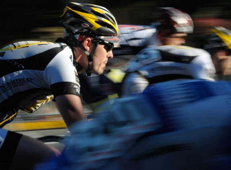 Redmond Derby Days. A pack of racing cyclists flash past with stretched out motion blur. One cyclist remains in tack-sharp focus as the sun paints him in light. © Jerry and Lois Photography, all rights reserved