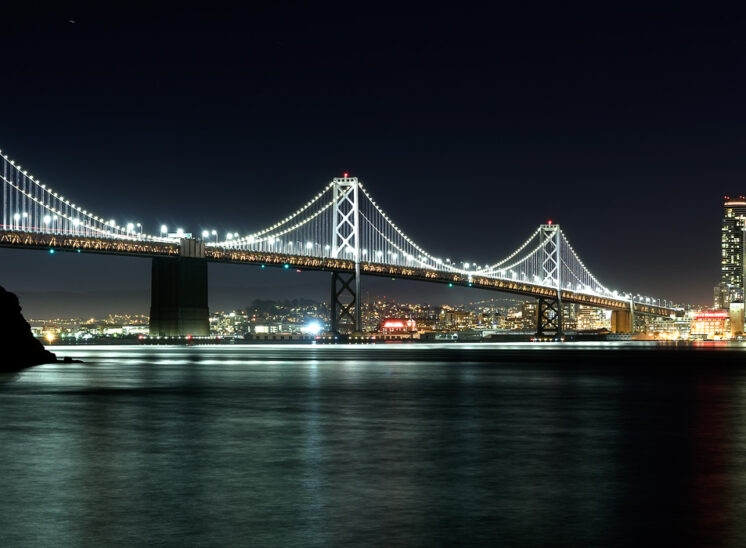 The Bay Bridge in lighting glory reflecting in the San Francisco bay with the City glowing in the night. Jerry and Lois Photography